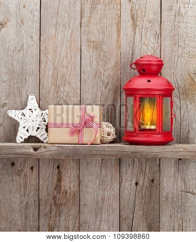 Christmas candle lantern and decor in front of wooden wall with copy space