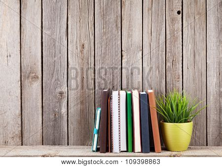 Wooden shelf with books in front of wooden wall. View with copy space