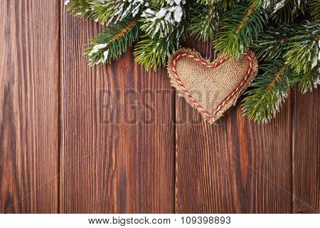 Christmas tree branch with snow and heart toy on wooden table. Top view with copy space