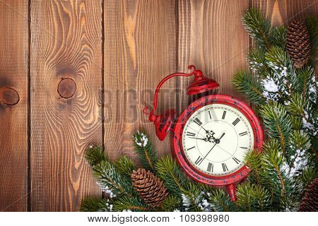 Christmas wooden background with clock, snow fir tree and copy space