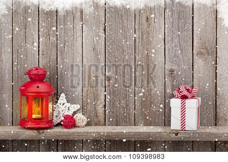 Christmas candle lantern, gift box and decor in front of wooden wall with copy space