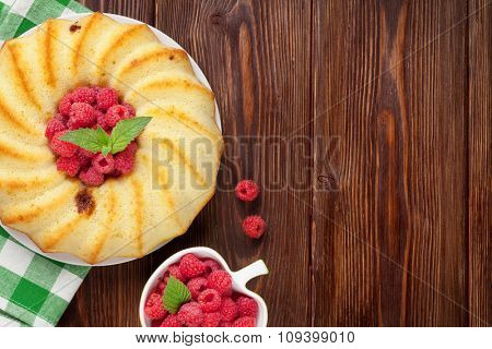 Homemade raspberry cake and berries on wooden table. Top view with copy space