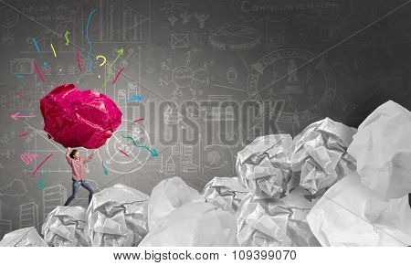 Woman carrying with effort big crumpled ball of paper as creativity sign