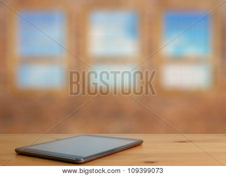 tablet on wooden table in old room with big windows
