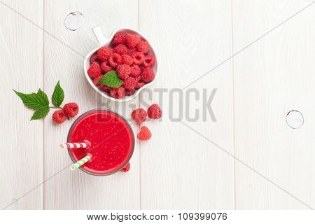 Raspberry smoothie and berries on wooden table. Top view with copy space