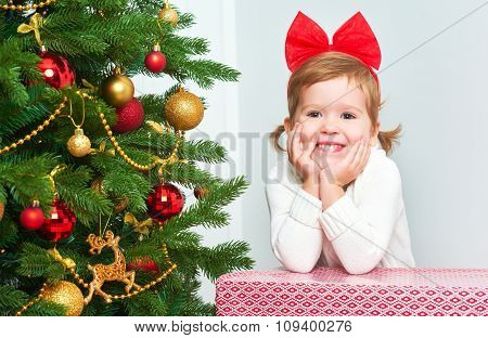 Happy Child With Christmas Gifts Near A Christmas Tree