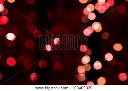 Abstract Blured Background Of Dark Red Shiny Christmas Tree Decorations At Night