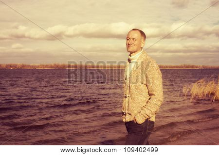 Happy Smiling Man, Wearing Casually, Walking Along The Beach, In Magic Autumn Day And Enjoying Life
