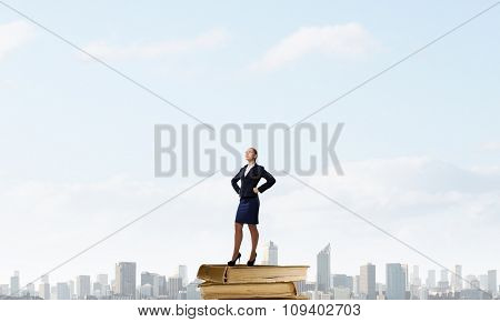 Confident businesswoman standing on pile of books
