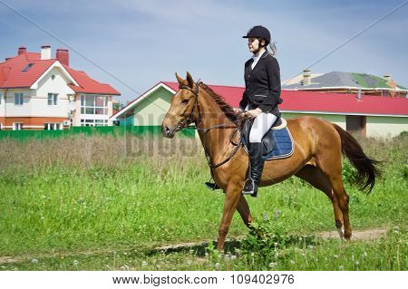 Beautiful young girl jockey riding horse