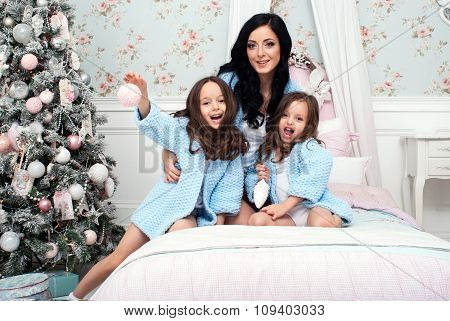 Woman with children blue knit cardigan in the bed near Christmas tree