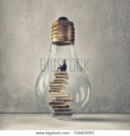 Young woman sitting om books stack inside of glass light bulb