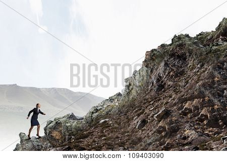 Young determined businesswoman climbing up mountain to reach top