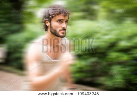 Man running fast in a park. Motion blur effect to give a dynamic look