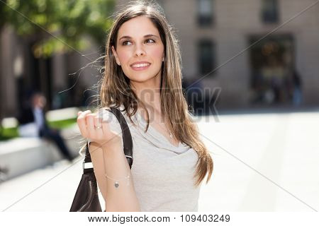 Portrait of a smiling woman walking in an urban street