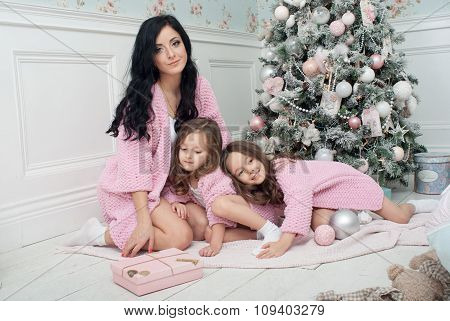 Young women with two girls of three and five around the Christmas tree