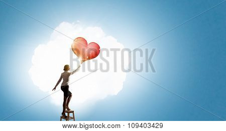 Businesswoman standing on chair and reaching red heart