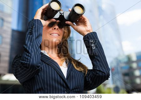 career woman looking with binoculars in the city
