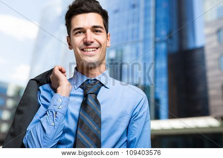 Young businessman holding his jacket outdoor