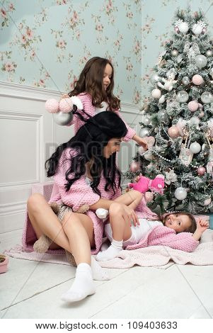 Woman with children pink knit cardigan in the bed near Christmas tree