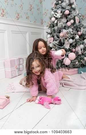 Two little girls around the Christmas tree