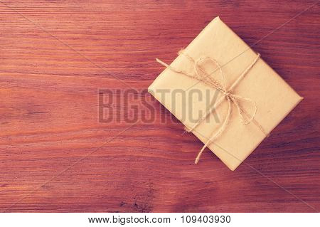 Gift Box Packed Into Brown Paper Tied By Twine On Old Wooden Table With Space For Text