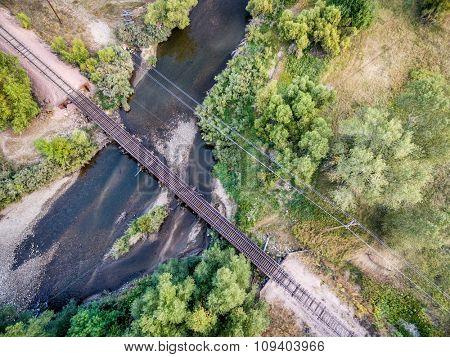 aerial view of single railroad tracks in back country crossing a river