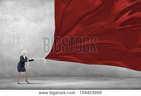 Woman in Santa suit pulling red clothing banner
