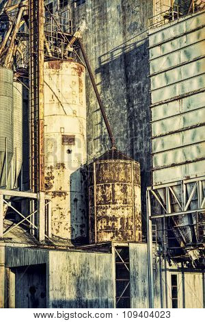 industrial background with grunge texture effect - exterior of old abandoned grain elevator with pipes, ducts, ladders and chutes