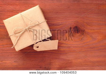 Gift Box Into Brown Paper Tied By Twine With Blank Tag On Old Wooden Table With Space For Text