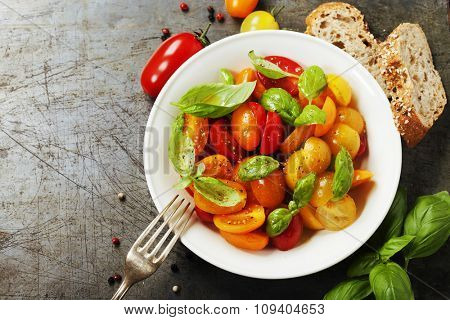 Fresh tomatoes with basil leaves in a bowl on vintage background.