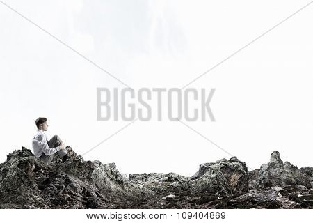 Young thoughtful businessman sitting alone on rock top