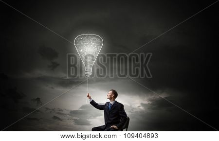 Businessman with bulb on rope representing bright idea