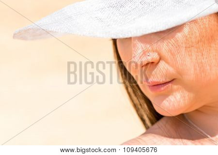 Woman's Face With The Shadow Of The White Hat Close-up