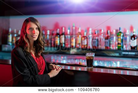 Beautiful brunette girl with cocktail sitting at bar counter