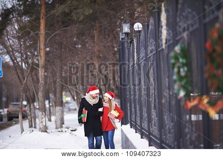 Happy couple in Santa hats with Christmas gifts walking outdoors