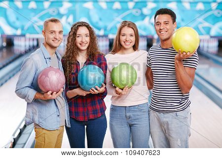 Group of four friends holding bowling balls and smiling