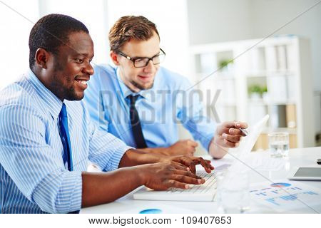 Two businessmen working together on a project sitting at a table in the office
