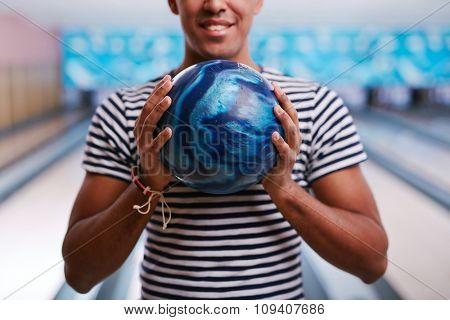 Young man holding bowling ball in his hands
