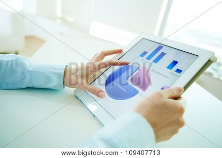 Female hands analyzing financial results with the help of a digital pad