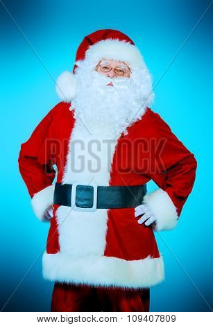 Portrait of a traditional Santa Claus over blue background. Studio shot. Christmas.