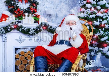 Traditional Santa Claus sitting in a rocking chair in the room by the fireplace and Christmas tree and smokes a pipe.