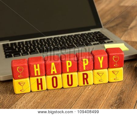 Happy Hour written on a wooden cube in a office desk
