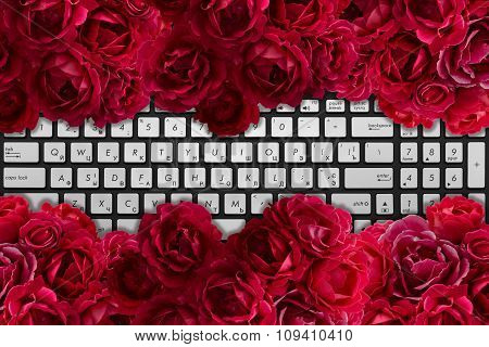 Modern Black And Chrome Laptop Keyboard With Bush Of Red Rose Flowers Background