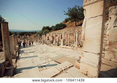 Tourists Wallking Past Alley Of Greek-roman City Ephesus With Stone Sculptures