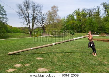 Young athlete man training in the park with huge wooden log.