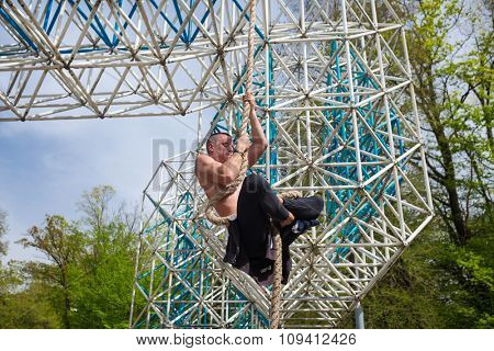 Young athlete man climbing the rope tied to metal construction.