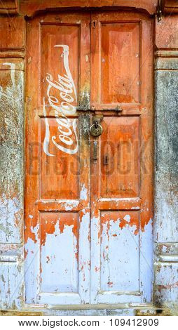 KATHMANDU, NEPAL - CIRCA NOVEMBER 2015: Vintage Coca-Cola advertisement painted on a wooden door.