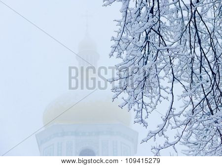 Branches Under Snow Against The Background Of Church
