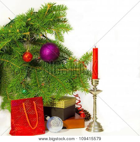 Branch Of A Decorated Christmas Trees, Candle  And Christmas Gifts